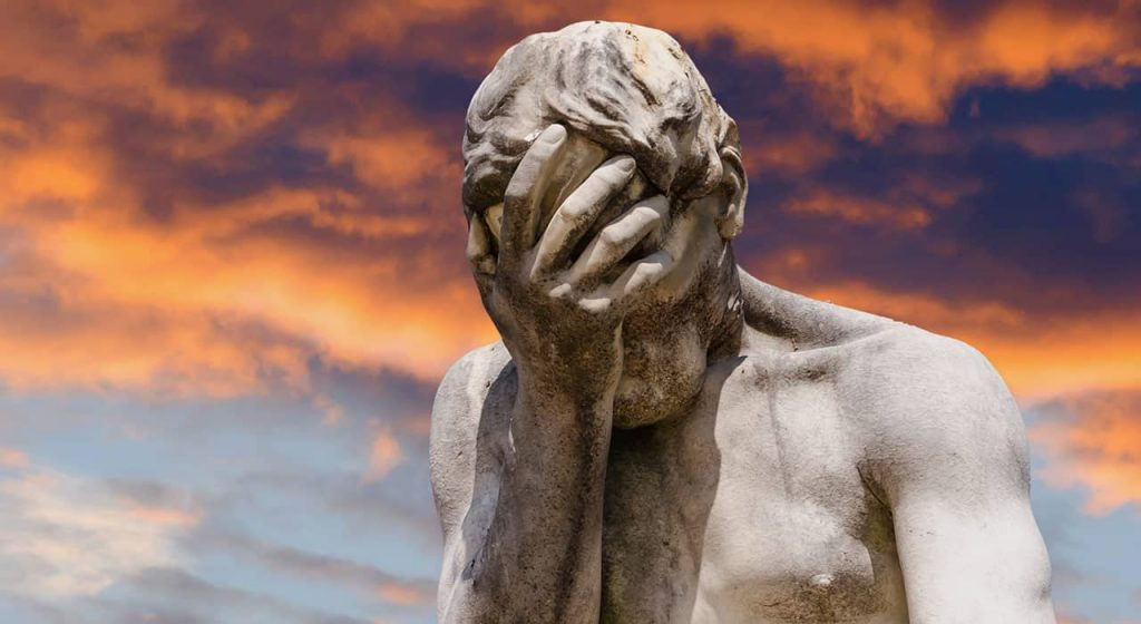 Image of a statue doing a face palm in front of a sunset
