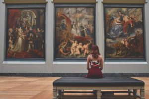 A woman staring at a wall of paintings at a Paris museum