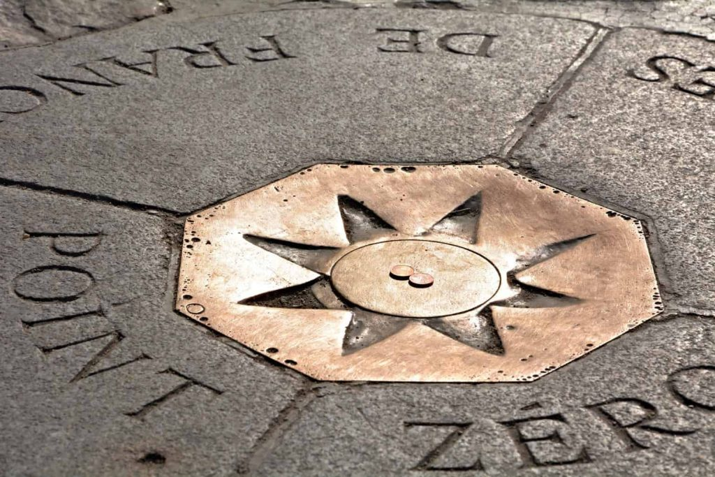 Coins sit in the middle of the Point Zero Plaque in Paris