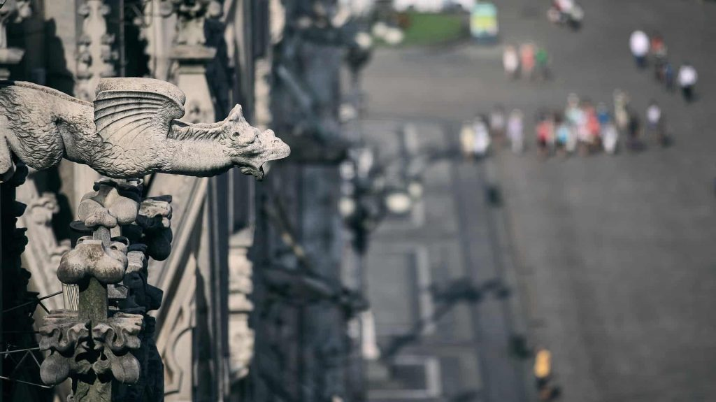 A close up of a gargoyle with people going on a tour in Paris in the background