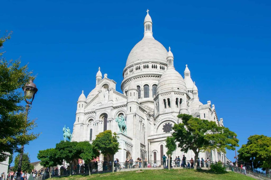 A photo of the Sacre Coeur on the top of Montmartre, one of the churches to visit in Paris