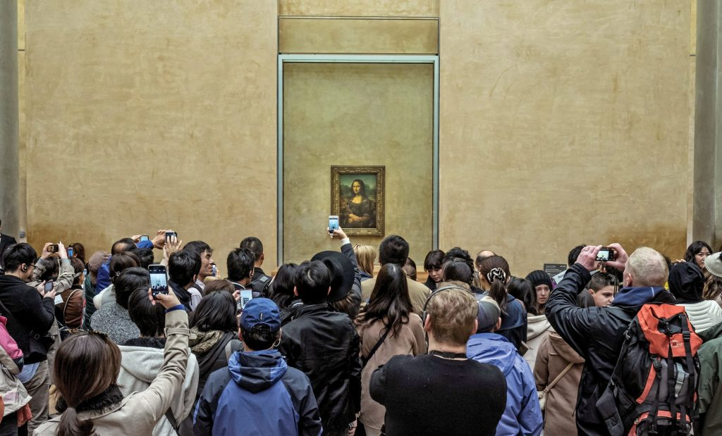 A photo of the crowds in front of the Mona Lisa, the reason 80% of people visit the Louvre