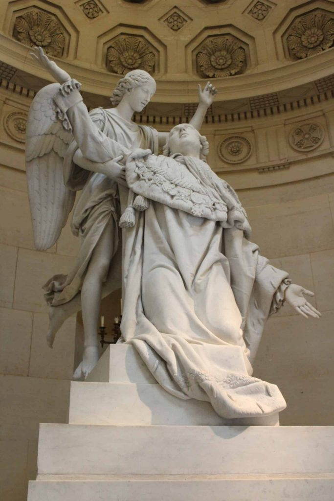 A photo of a statue of Louis XVI being supported by an angel in the Chapelle Expiatoire.