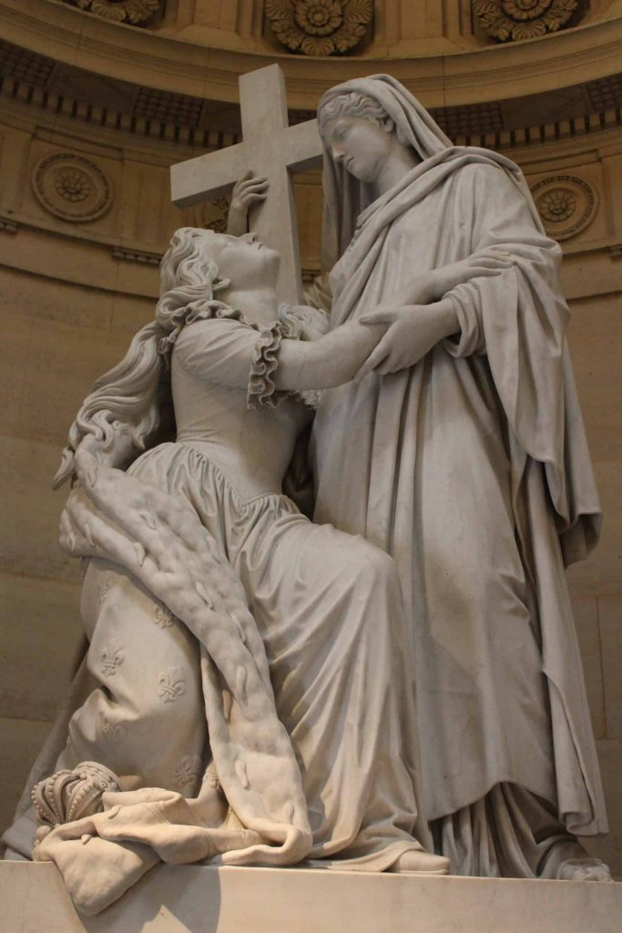 A photo of a statue of Marie Antoinette looking up a representation of religion.