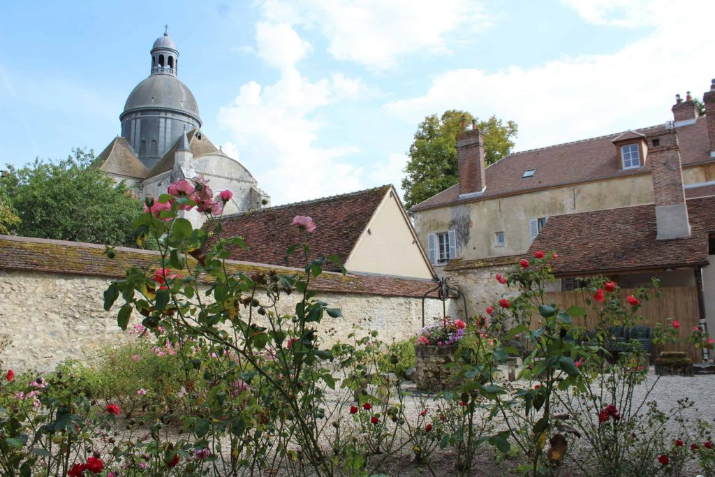 A photo of a rose garden in Provins with the Saint Quiriace Collegiate Church in the background.