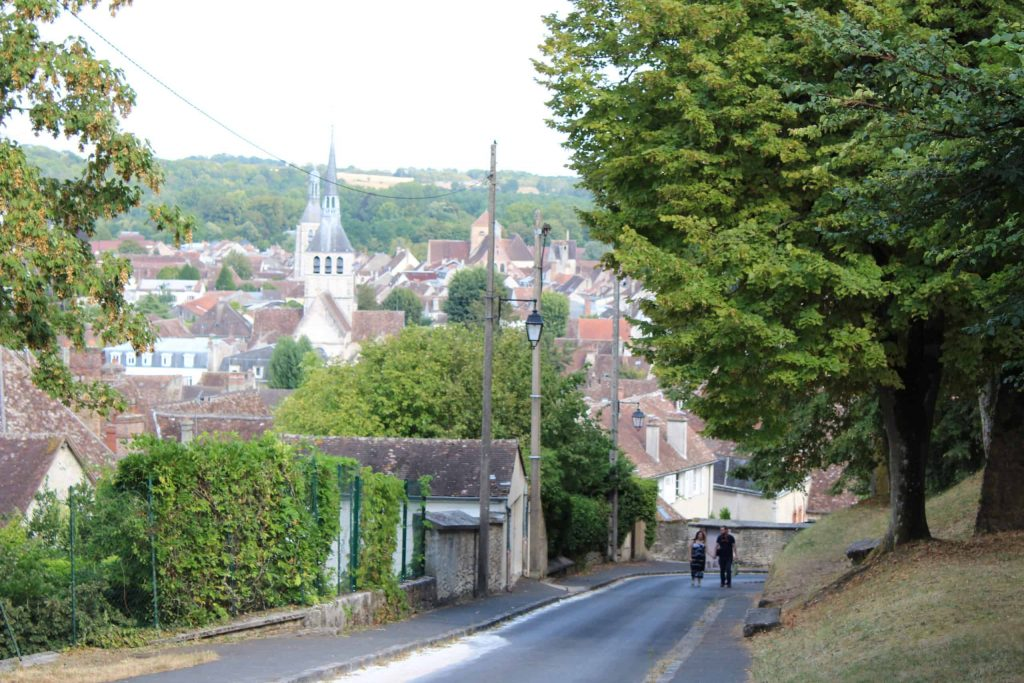 A photo of a road heading down the hill from the old town of Provins, with a view of the lower town in the distance.