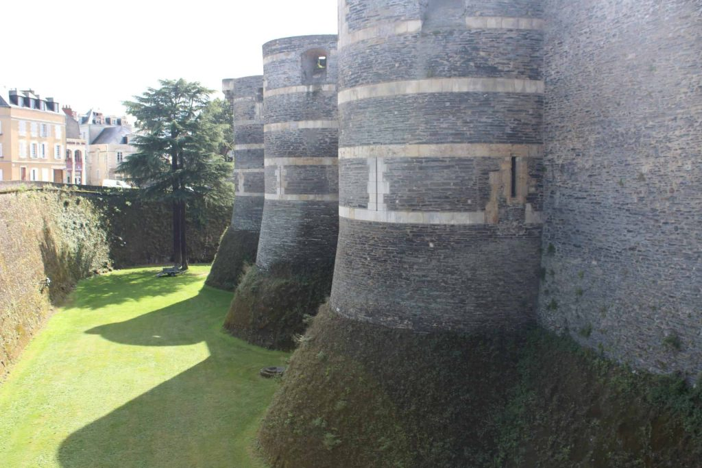 A photo of the walls and towers of the Angers Chateau, with the manicured lawns in the moat below.