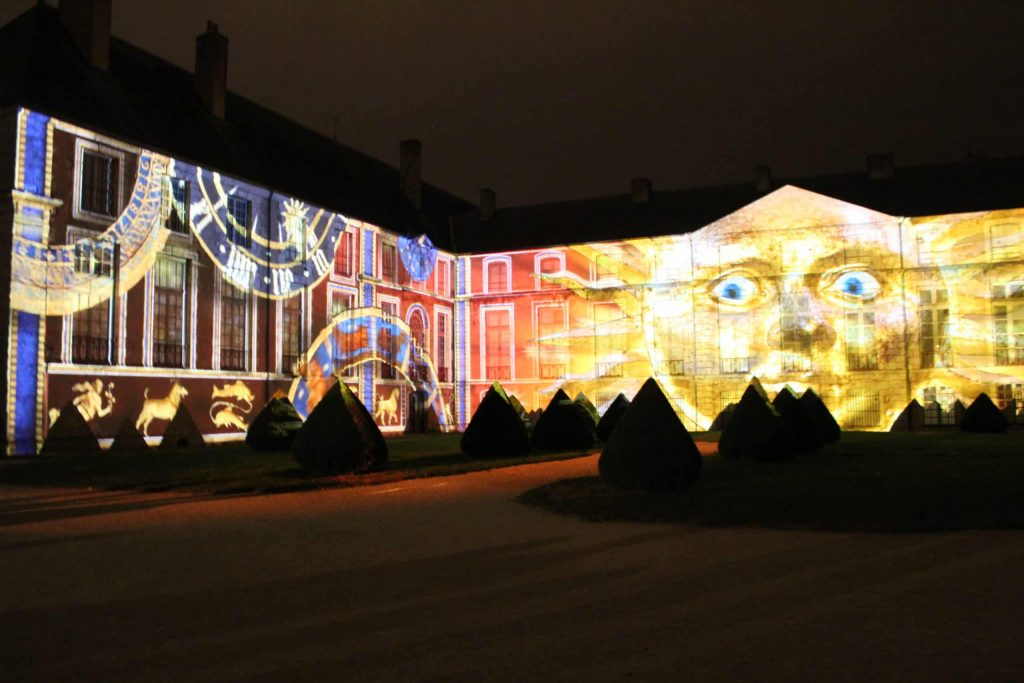 A photo of the light projections of a sun with a face and clocks on the side of a building during Chartres en Lumières.