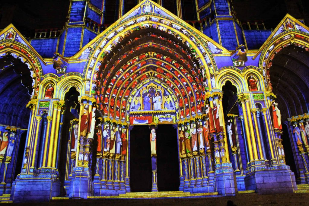 A photo of one of the cathedral portals illuminated during Chartres en Lumières