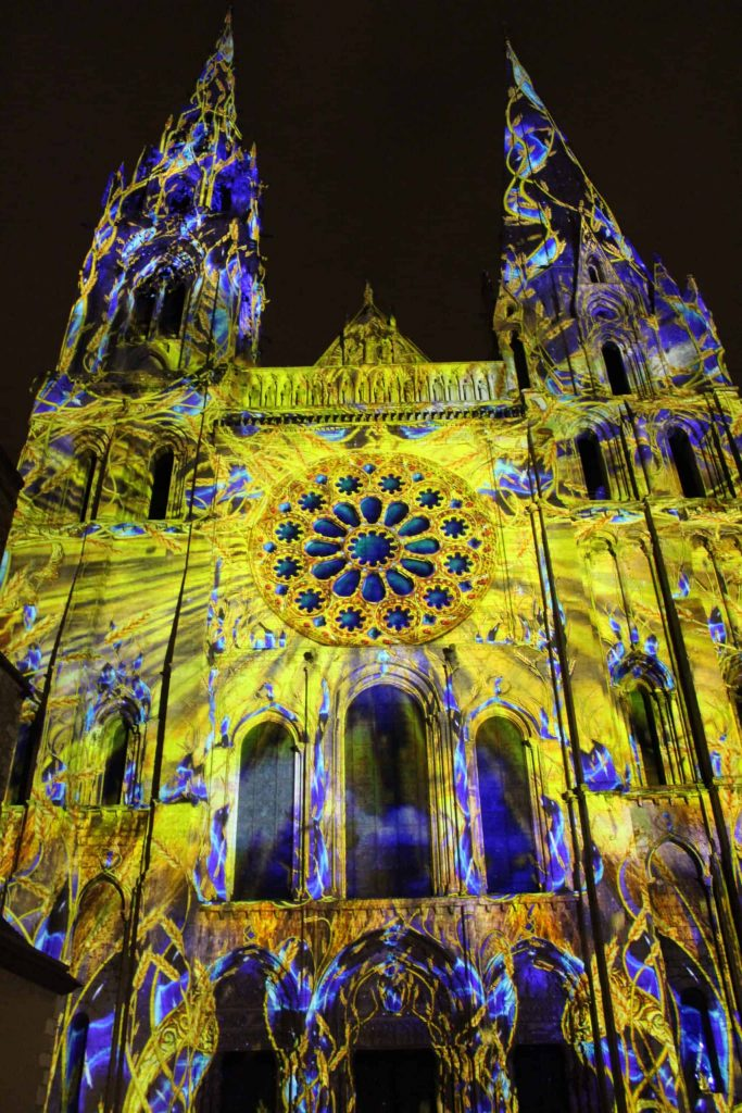 A photo of the western facade of the cathedral illuminated during Chartres en Lumières