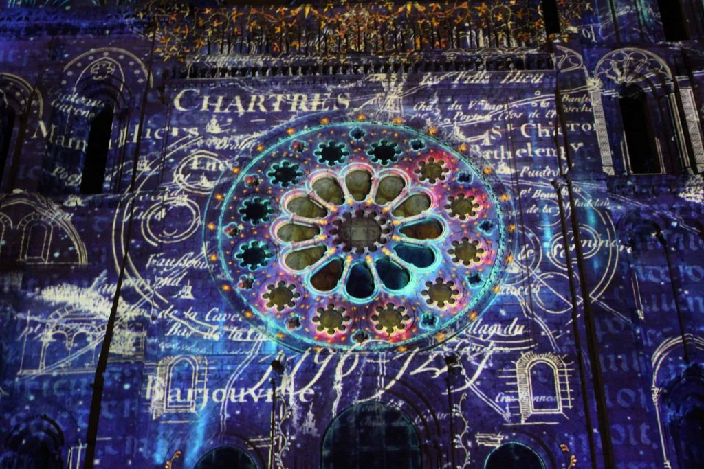 A photo of the western Rose window illuminated during Chartres en Lumières.
