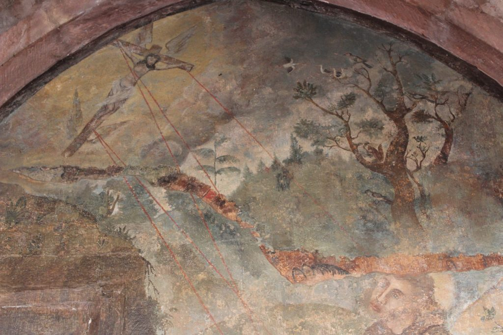 A photo of the mural in the cloisters that depicts a flying Jesus on a cross with what appears to be laser beams shooting out from the nails.