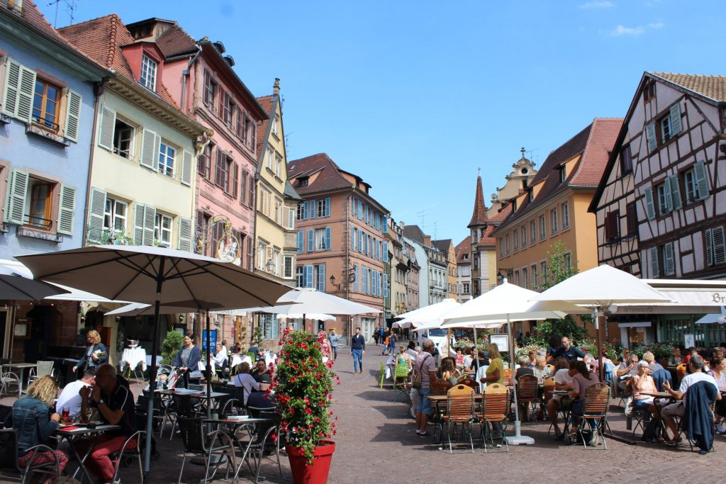 A photo of a plaza in Colmar, covered in restaurant terraces, and surrounded by the half-timbered houses.
