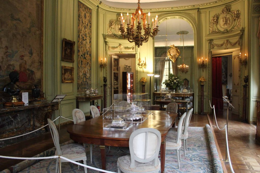 A photo of the dining room with a chandelier hanging above the main table.