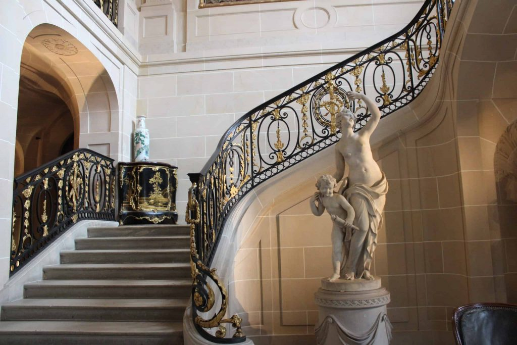 A photo of the grand stairwell of the Musée Nissim de Camondo with a statue of a woman and child at the base.