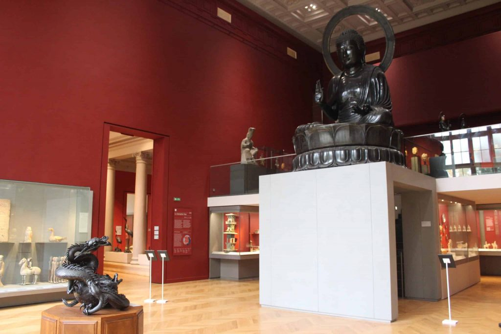 A photo of the great hall of the Musee Cernuschi, with the large Buddha looking down over the incense burner.
