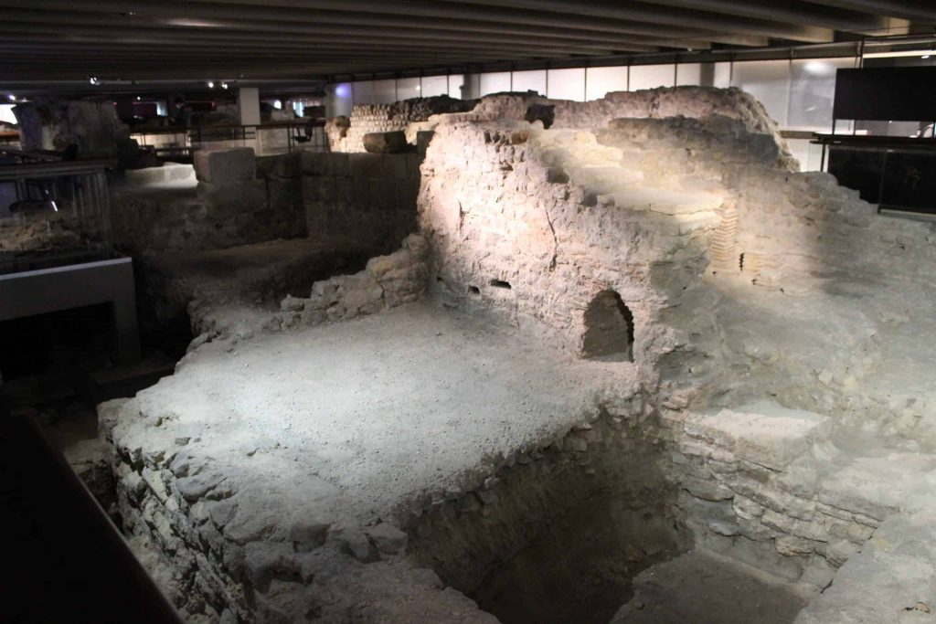 A photo of the ruins in the archeological crypt, including some walls and a small archway.
