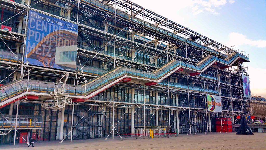 A photo of the front facade of the Centre Pompidou, with the exterior escalator clearly running up the side of the building.