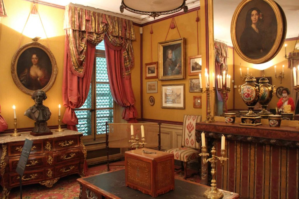 A photo of the Salon George Sand, with a portrait of the artist featured prominently over the mantle.