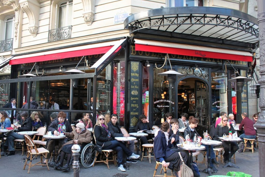 A photo of a staple of Parisian living, people enjoying a drink or a meal on a Parisian terrace.