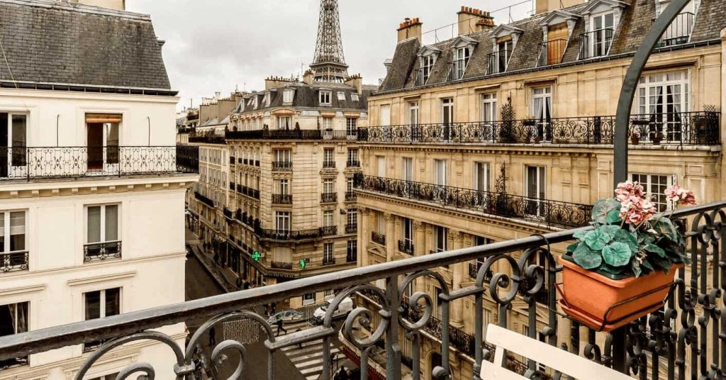 A photo taken from the balcony of a Parisian apartment, looking down the block at other Parisian apartments, with the Eiffel Tower in the distance.