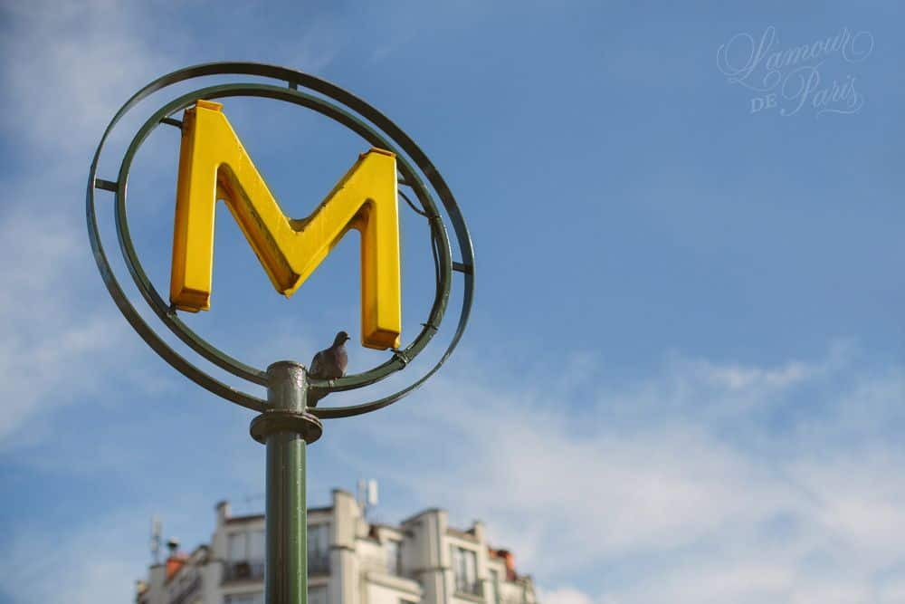 A photo of a modern Paris Metro sign with a yellow M surrounded by two metal circles.