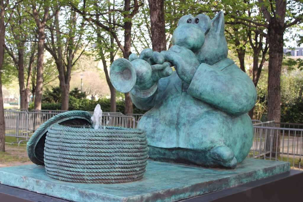 A bronze statute by Philippe Geluck of a cat playing a horn. A basket is in front of the cat with a fountain spouting from the middle.