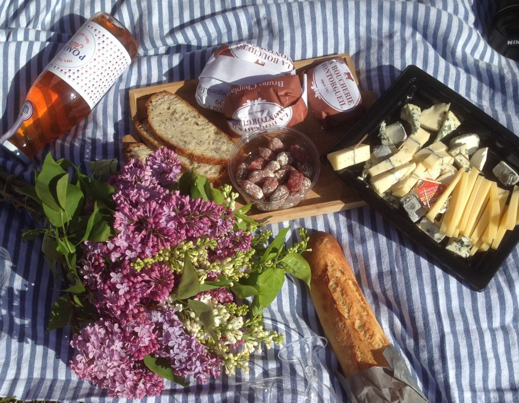 A photo from one of the top places to picnic in Paris. It is a close up of cheese, bread, wine, and charcuterie on a picnic blanket, along with a bouquet of purple and green flowers.