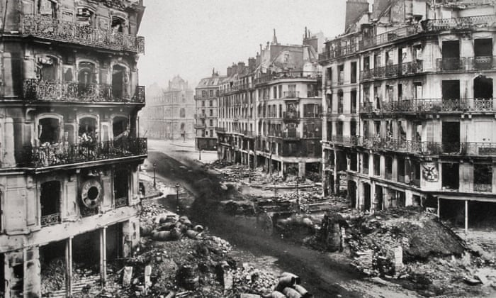 A black and white photo from the final bloody week of the Paris Commune. The photo shows Rue de Rivoli in Paris, buildings burnt out, and heaps of rubble on the sidewalks.