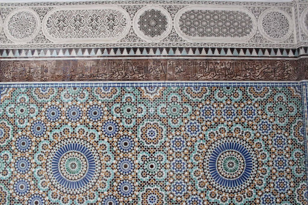 A close up photo of the detailed tile mosaics and carved stucco patterns of the walls of the mosque.
