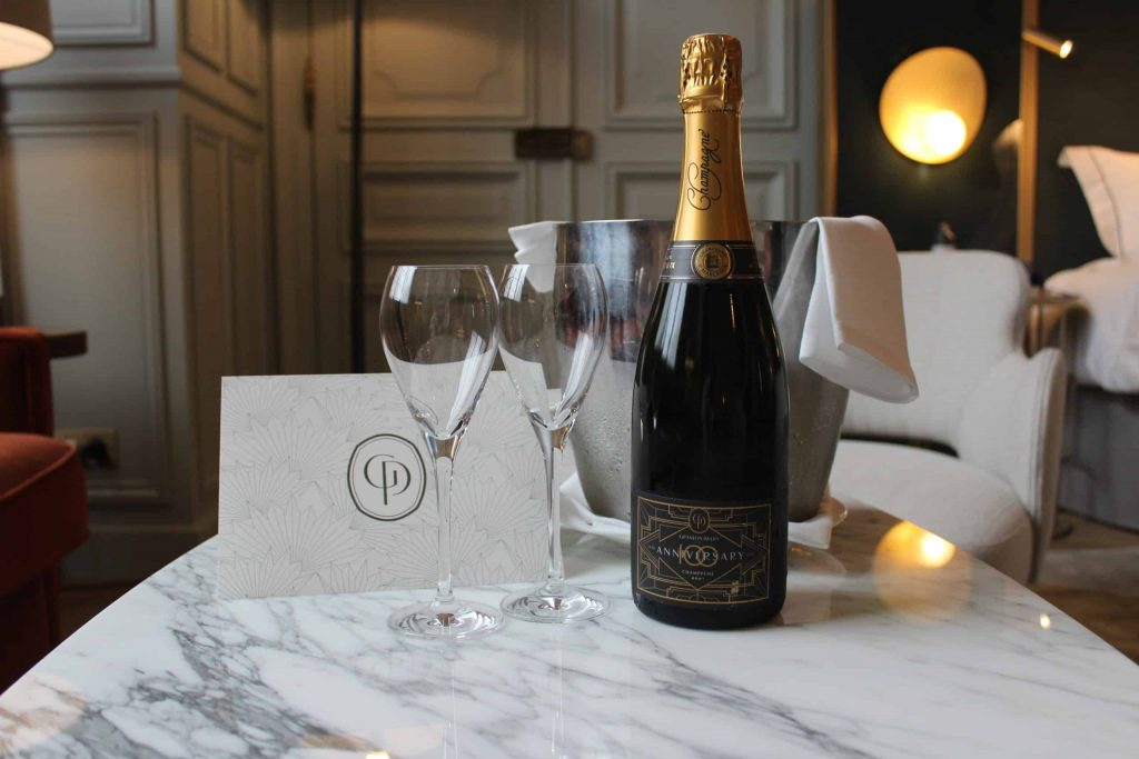 A photo of a champagne bottle, ice bucket, and two champagne glasses on a marble coffee table.