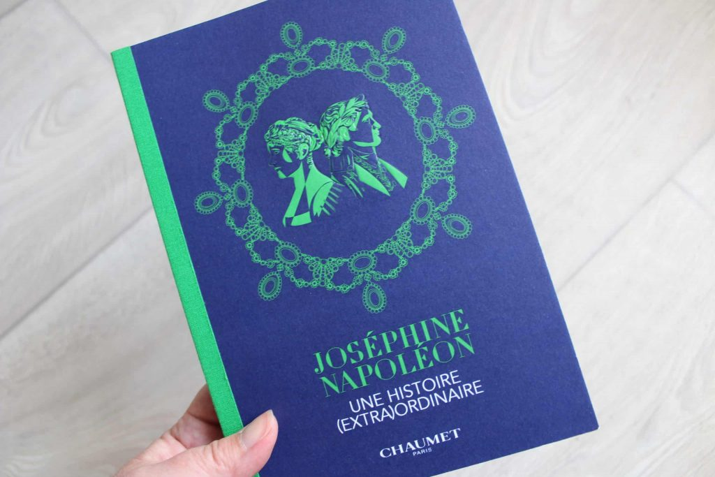 A close up photo of the program for the Chaumet exhibition Joséphine & Napoléon: Une Histoire (Extra)Ordinaire. The booklet is blue with green writing.