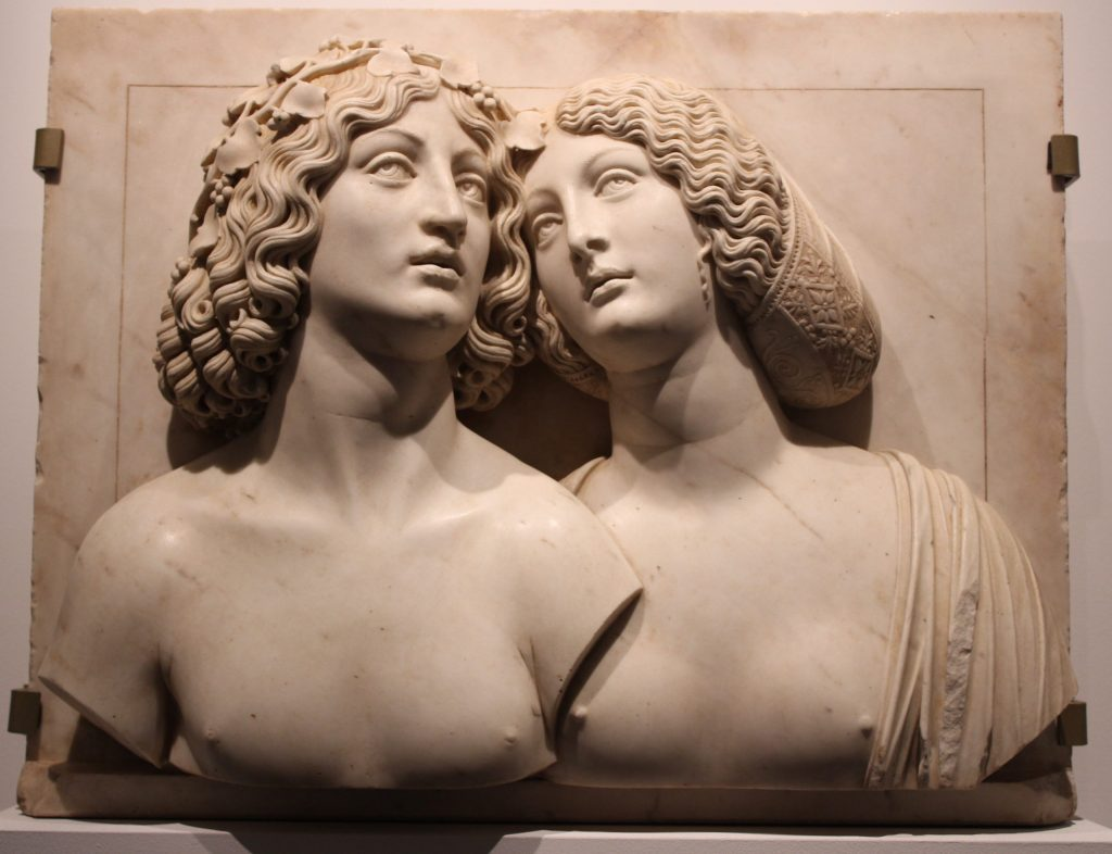 A photo of two sculpted busts with their heads together, looking off into the distance.