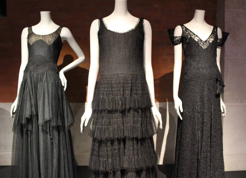 A close up photo of three black dresses displayed at the Palais Galliera as part of the Gabrielle Chanel exhibition.