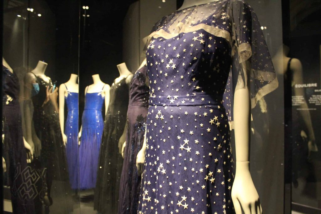 A photo of several blue evening gowns by Chanel, on display at the Palais Galliera.
