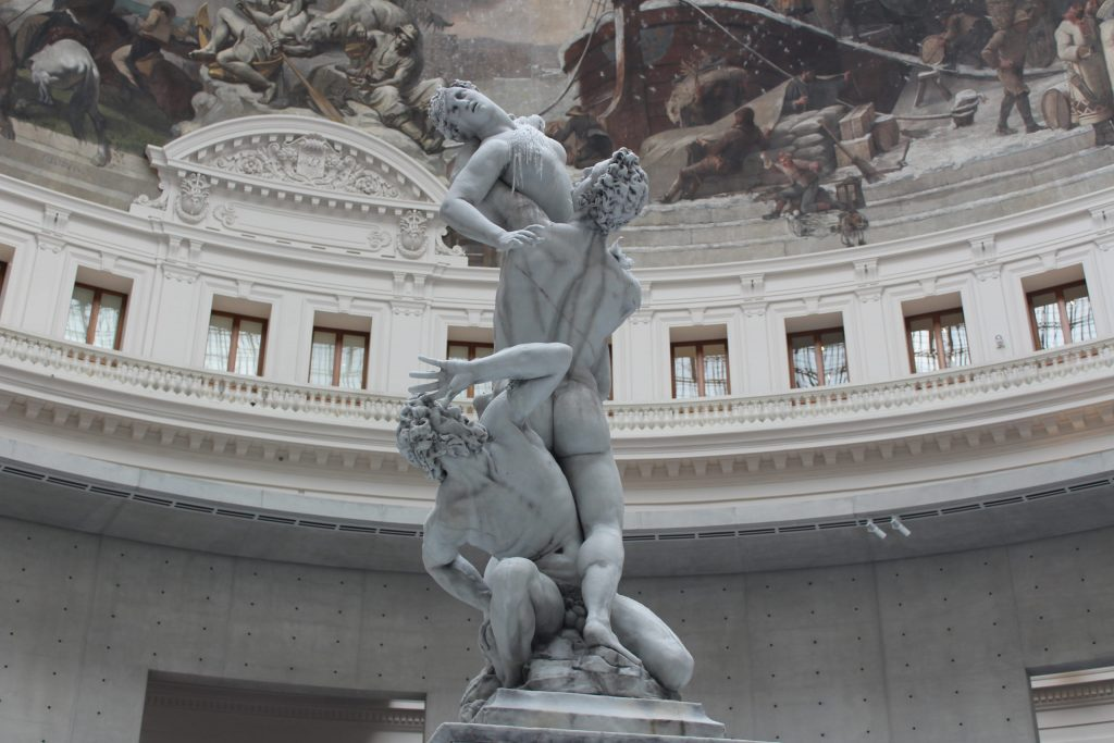 A photo of a wax sculpture replica of Giambologna's The Abduction of the Sabine Women. The sculpture has already been lit, and therefore wax trails over the chest of the woman, and her upper arm has melted away.