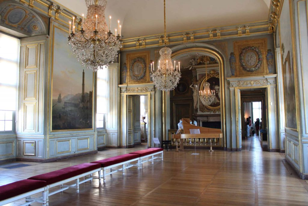 A photo of the Salle des Fetes, looking down towards the harpsichord in the musician's gallery at the end. The floors are wooden, the walls are covered in paintings, and three large chandeliers hang from the ceiling.