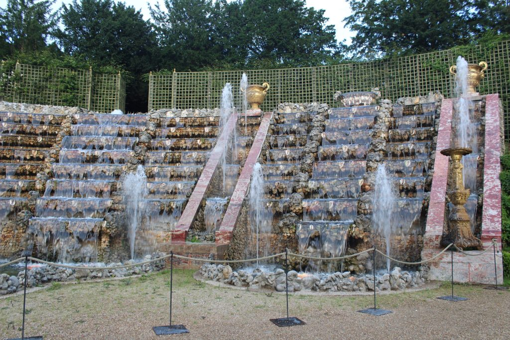 A photo of the layered waterfalls and fountains in the Ballroom Grove at the Chateau de Versailles.