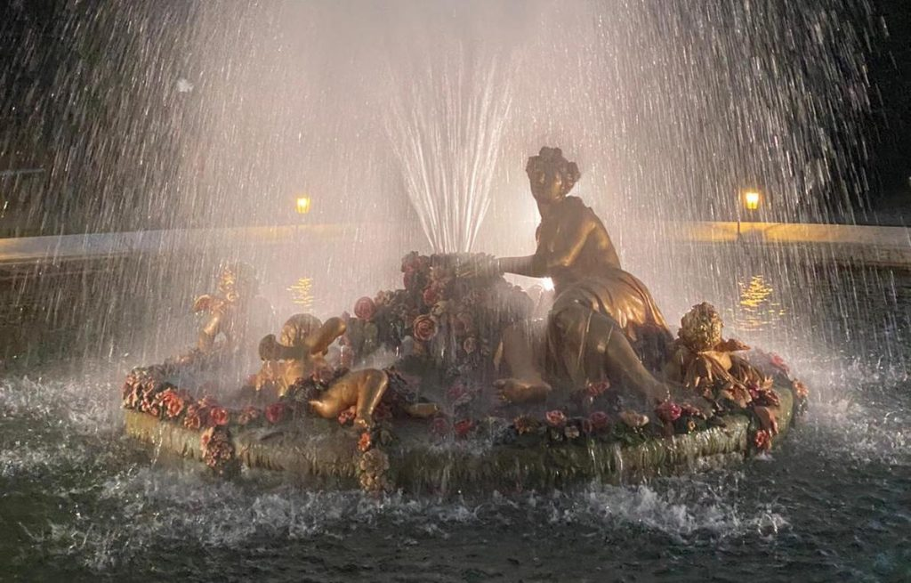 A photo of a fountain with water spraying into the air and being backlit by a white light.