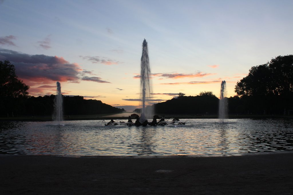 A photo of the Apollo fountain with the sunsetting in the background.