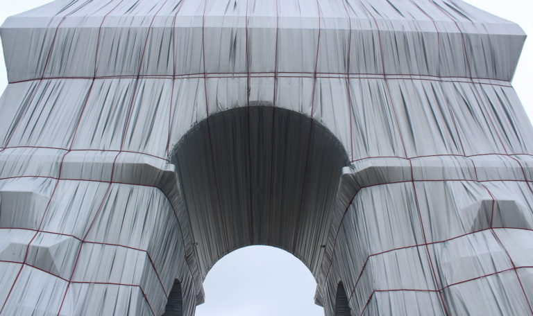 A close up photo of the Arc de Triomphe Wrapped, looking up at the Arc from the centre at street level.