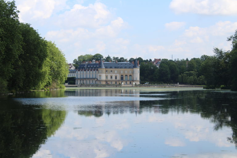 A photo of Château de Rambouillet in the distance. The photo was taken looking across a lake at the chateau.