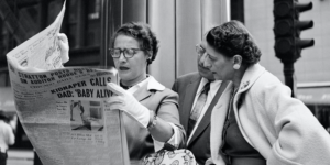 A black and white photograph of two women looking at a newspaper.